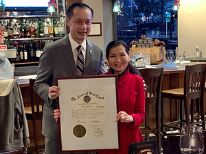 Outgoing Deputy Secretary of Commerce Ben Wu receives a commendation presented by First Lady Yumi Hogan.