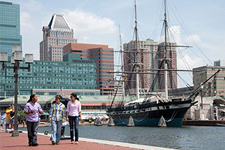 Three people walking along Baltimore's Inner Harbor