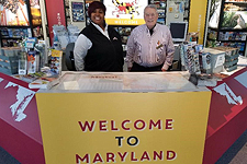 Two Welcome Center staff standing behind the counter at one of the Maryland Welcome Centers