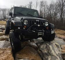 A Jeep climbing through a rocky cliff.