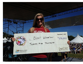 Blair Wheeler holding up a check for the Diamond Jim award