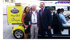 Terry Hasseltine, Maryland Office of Sports Marketing, with Lisa Furfine and Tim Schneider, Sports Travel magazine, stand by one of the Team Maryland-sponsored e-cruisers at the TEAMS Conference & Expo in Detroit.