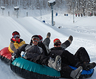 A group of people tubing down a snow slope at Wisp.