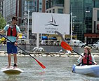 Guy standup paddle boarding and a girl kayaking