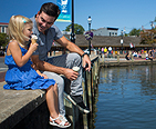 A father and daughter sitting on a ledge overlooking the water and eating ice cream in downtown Annapolis.
