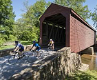 Three people bike riding through a covered bridge.