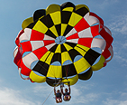 A couple parasailing with a Maryland flag parachute