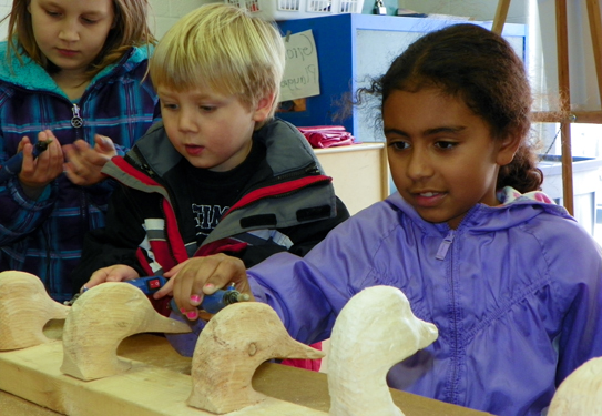 children looking at wooden duck head carvings