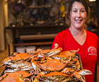 Waitress serving a tray of steamed crabs