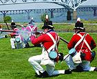 Reenactors firing their rifles